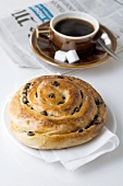 Raisin roll, coffee and newspaper