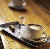 Cappuccino und Grappa auf Tablett