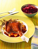 Goose leg with pieces of pear and red cabbage