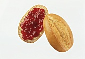 A bread roll with jam against a white background