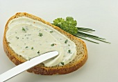 A slice of bread with herb soft cheese