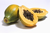 Papayas, one whole and one halved