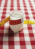 A jar of yoghurt with a tape measure wrapped around it