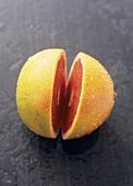 A pink grapefruit, cut in half