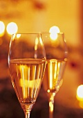 Two glasses of sparkling wine in subdued light