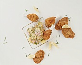 Fried chicken pieces with potato salad