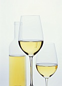 Glasses of white wine in front of bottle
