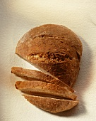 A loaf of bread, partly sliced