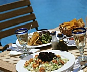 Prawn salad and crisps on laid table out of doors