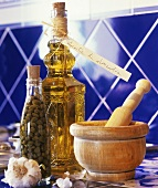 Garlic, bottle of capers, bottle of almond oil & wooden mortar & pestle