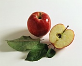 A whole red apple and half a red apple with leaves