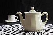 Teekanne und Teetasse auf Tischtuch mit Zebramuster