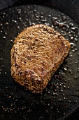 Fried peppered steak in frying pan