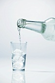 Pouring vodka into glass containing ice cubes