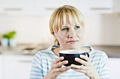 Blond woman holding a giant coffee mug