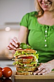 Woman garnishing a multilayer sandwich with basil