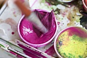 Stirring water colors with a brush