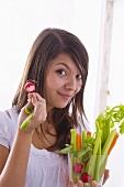 Mädchen hält rohes Gemüse und angebissenes Radieschen