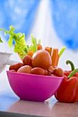 Tomaten in pinkfarbener Schale, Paprikaschote, Möhren, Sellerie