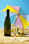 Glass and bottle of white wine in a summery setting