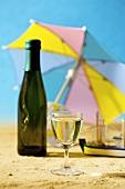 Glas und Flasche Weisswein in einer sommerlichen Kulisse