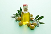 A small bottle of olive oil with olives and olive sprigs