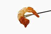 Shrimp Dipped in Cocktail Sauce on Fork; White Background