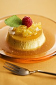 Flan with Fruit Sauce and Fresh Raspberry Garnish