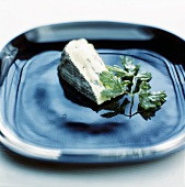 A piece of raw milk cheese with fried parsley