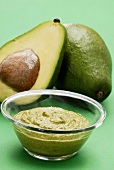 Guacamole with avocados in the background