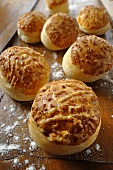 Several cheese bread rolls on a floured surface