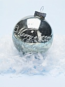 Antique silver Christmas bauble on artificial snow