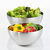Peppers and green salad in stainless steel bowls