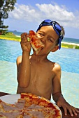 Boy with swimming goggles on head eating pizza on beach