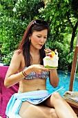 Frau trinkt Kokosmilch am Pool