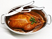 Roast goose in roasting dish, carving knife and fork