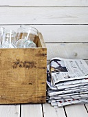 Empty glasses in wooden box beside pile of newspapers