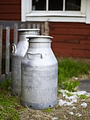 Milk churns in front of a wooden house
