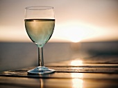 Glass of white wine on table against setting sun