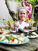 Little girl at smorgasbord in garden (Sweden)