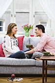Pregnant woman and man sitting on sofa