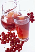 Redcurrant juice in glass and jug