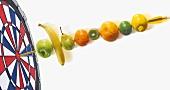 Fruit skewer and dartboard, close-up