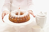 Woman holding out birthday cake with one candle
