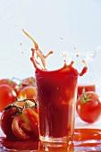 Tomato juice splashing out of glass