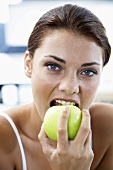 Young woman biting into a green apple