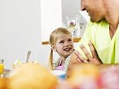 Vater und Tochter sitzen am Frühstückstisch