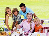 Family with baby at breakfast table in garden