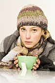 Woman in winter clothes with a bowl of tea