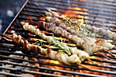 Belly pork kebabs with rosemary on barbecue